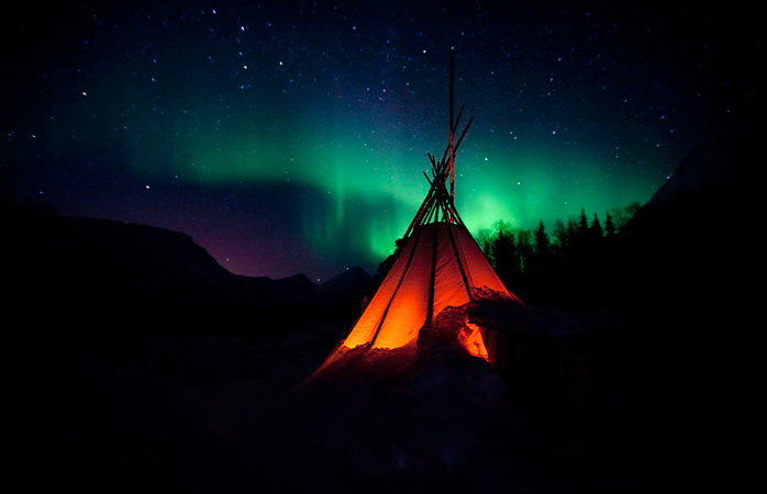 A typical Norwegian lavvo tent under the Aurora