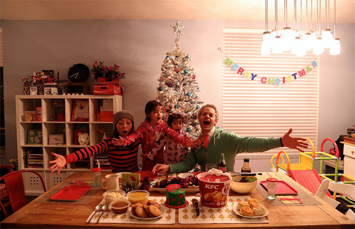 A family get ready to tuck into a KFC share bucket, a pretty bizarre Japanese Christmas tradition