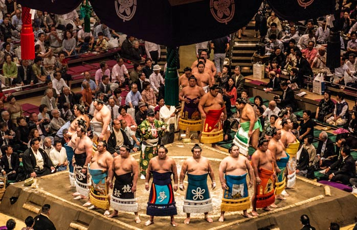 Sumo wrestlers gather for the ring-entering ceremony before a bout at Ryogoku