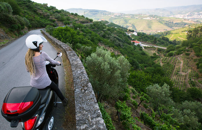 A woman travels by scooter overlooking the Douro Valley
