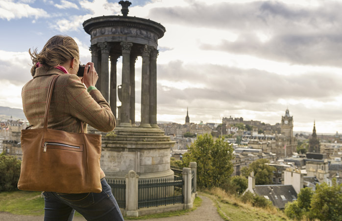 A woman takes a photo of Edinburgh from Calton Hill