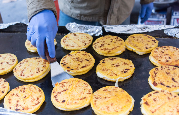Fresh arepas with cheese are cooking on the grill in Colombia